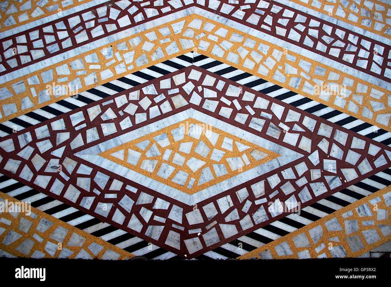 Geometrical design of marble mosaic flooring with orange, black and brown colored cement filling - Stock Image