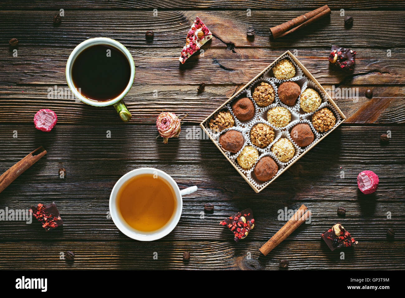 Sweet desserts: chocolate truffles, chocolate candy barks, cup of coffee, cup of green tea, cinnamon stick and coffee - Stock Image