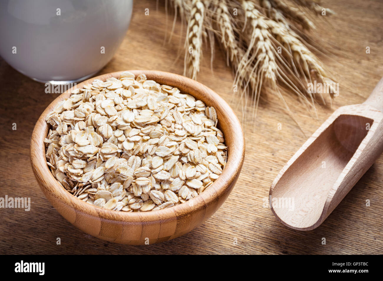 Rolled oats (oat flakes), milk and golden wheat ears on wooden background. Raw food ingredients, healthy lifestyle, - Stock Image