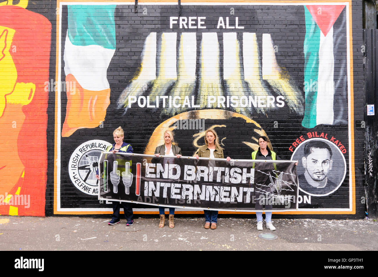 Four women hold a banner calling for the end of British Internment, while standing beside the IRPWA mural calling Stock Photo