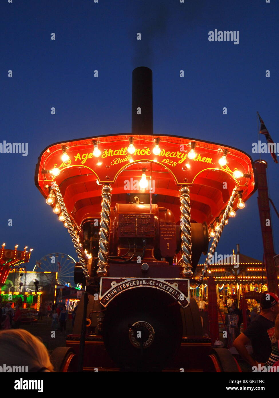 This is the front of a showmans steam traction engine lit up by its own generator and light bulbs, fun fair in the - Stock Image