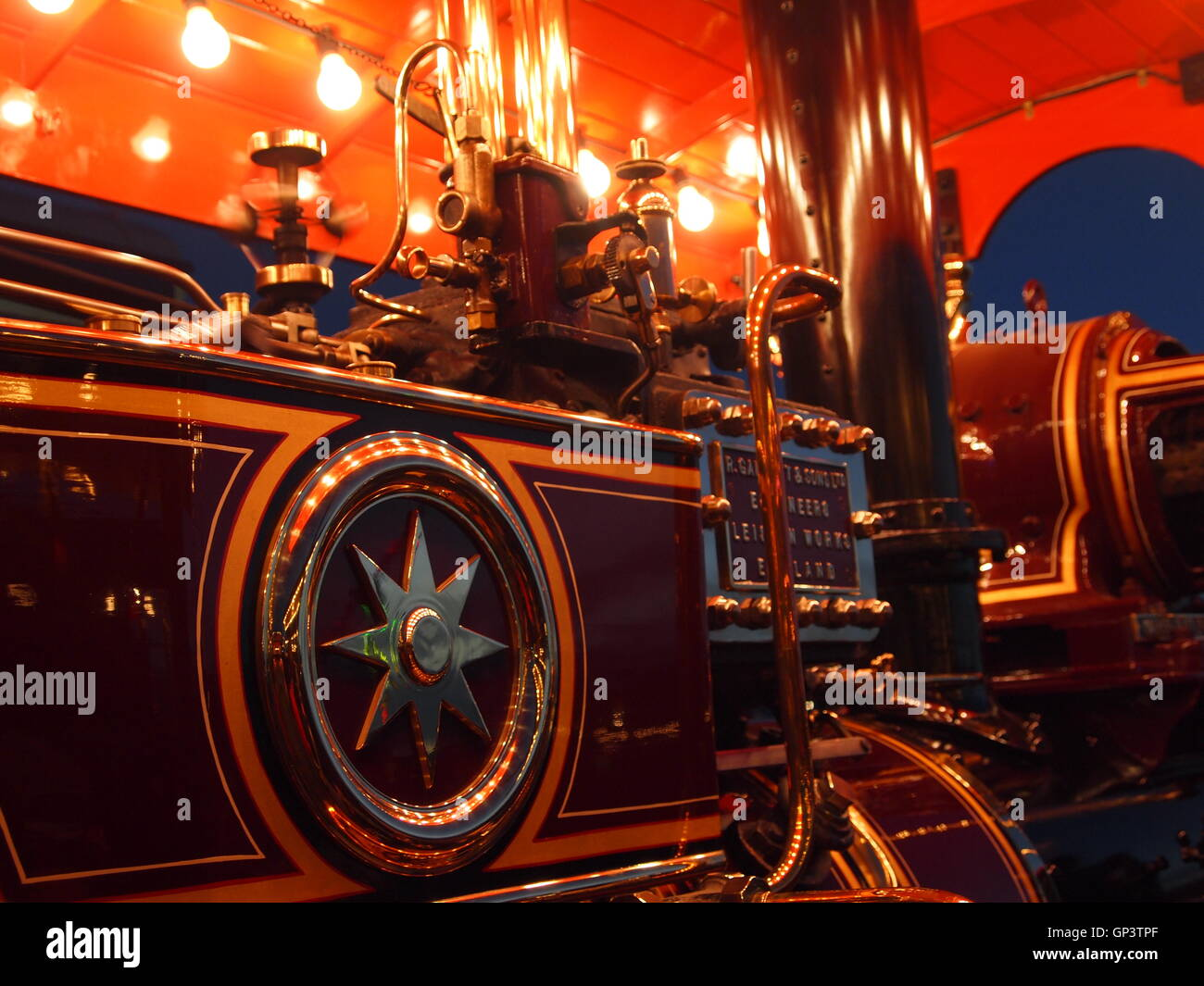 Close up of a section of a Showmans engine lit up at night - Stock Image