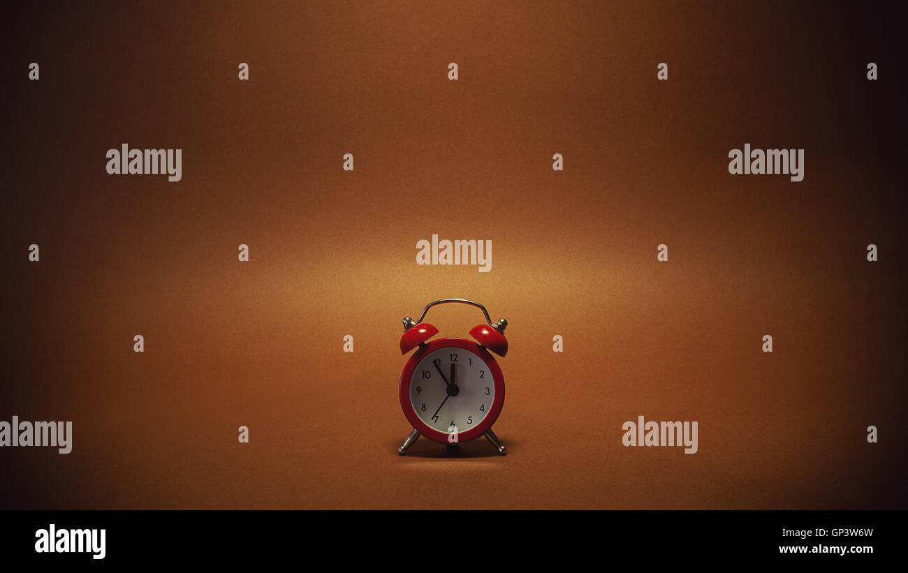Small red clock showing that there is only 5 minutes left, on brown background. - Stock Image