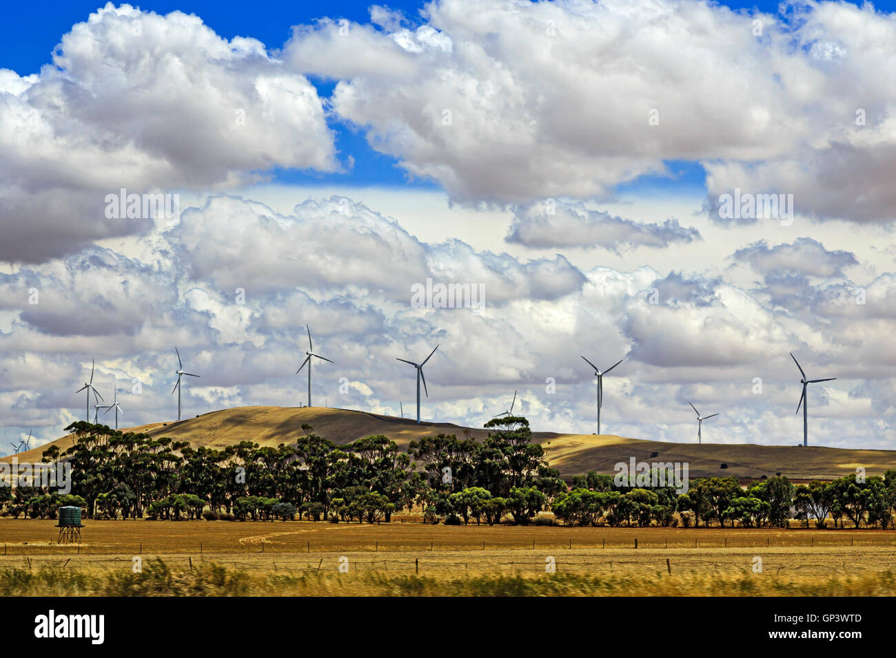 Chain of powerful tall wind turbines on top of hill chain in South Australia behind cultivated agricultural field - Stock Image
