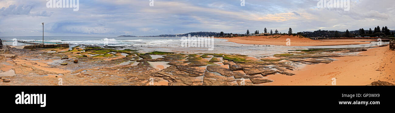 From rock pool to long clean Collaroy beach behind Narrabeen lake ocean entrance point in wide panorama at sunrise. - Stock Image
