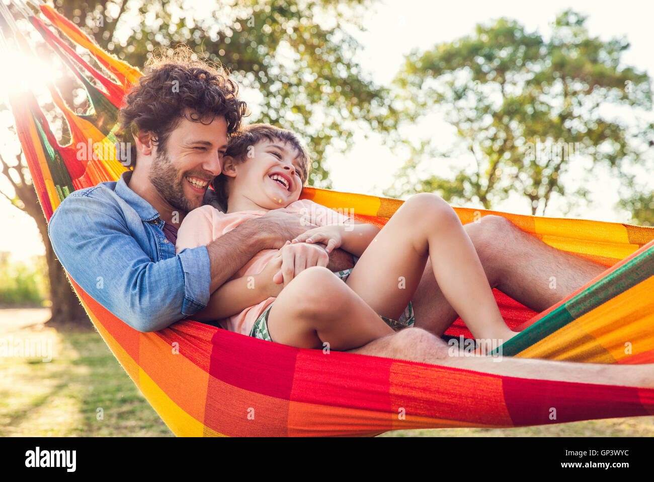 Father and son relaxing together in hammock - Stock Image
