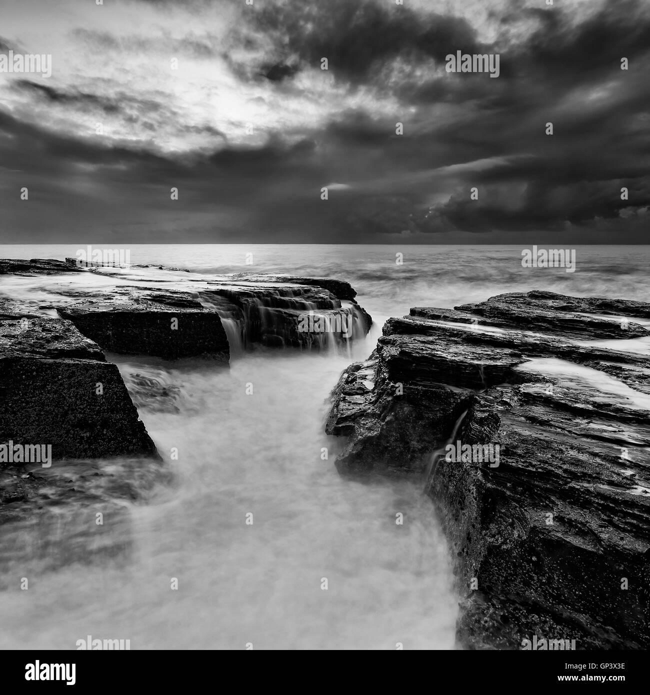 Pacific ocean waves erosion of Australian coastline at Sydney Northern beaches. Crack in sandstone boulders under - Stock Image