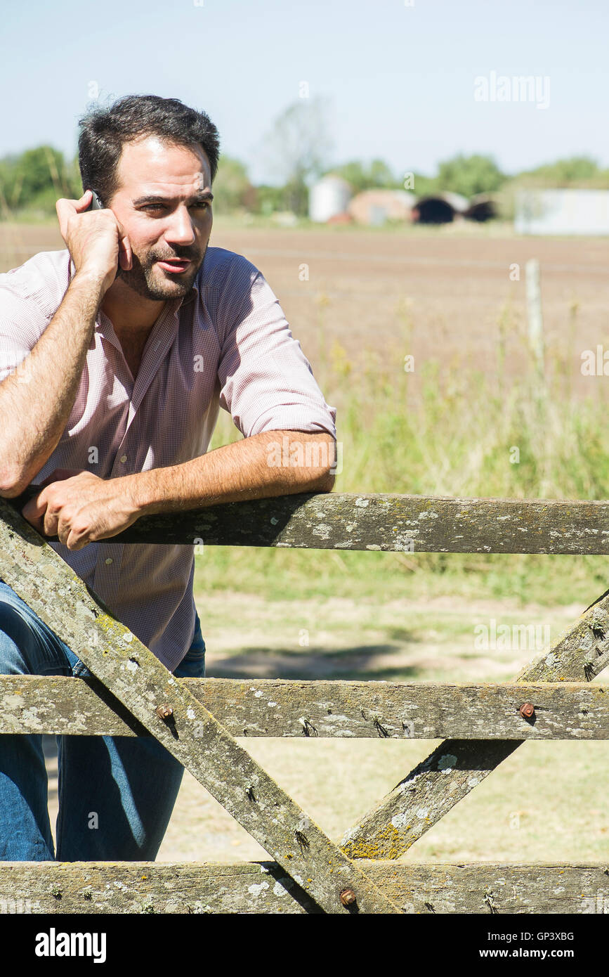 Farmer chatting on cell phone while surveying fields Stock Photo