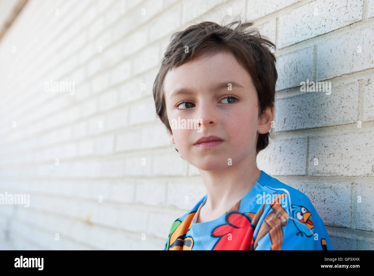 Boy looking away in thought, portrait - Stock Image