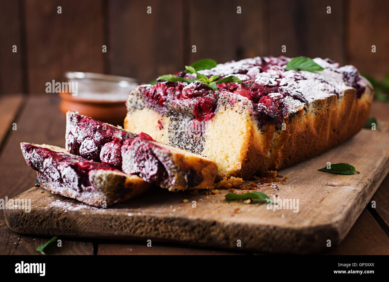 Cherry poppy seed cake dusted with powdered sugar on a wooden table - Stock Image