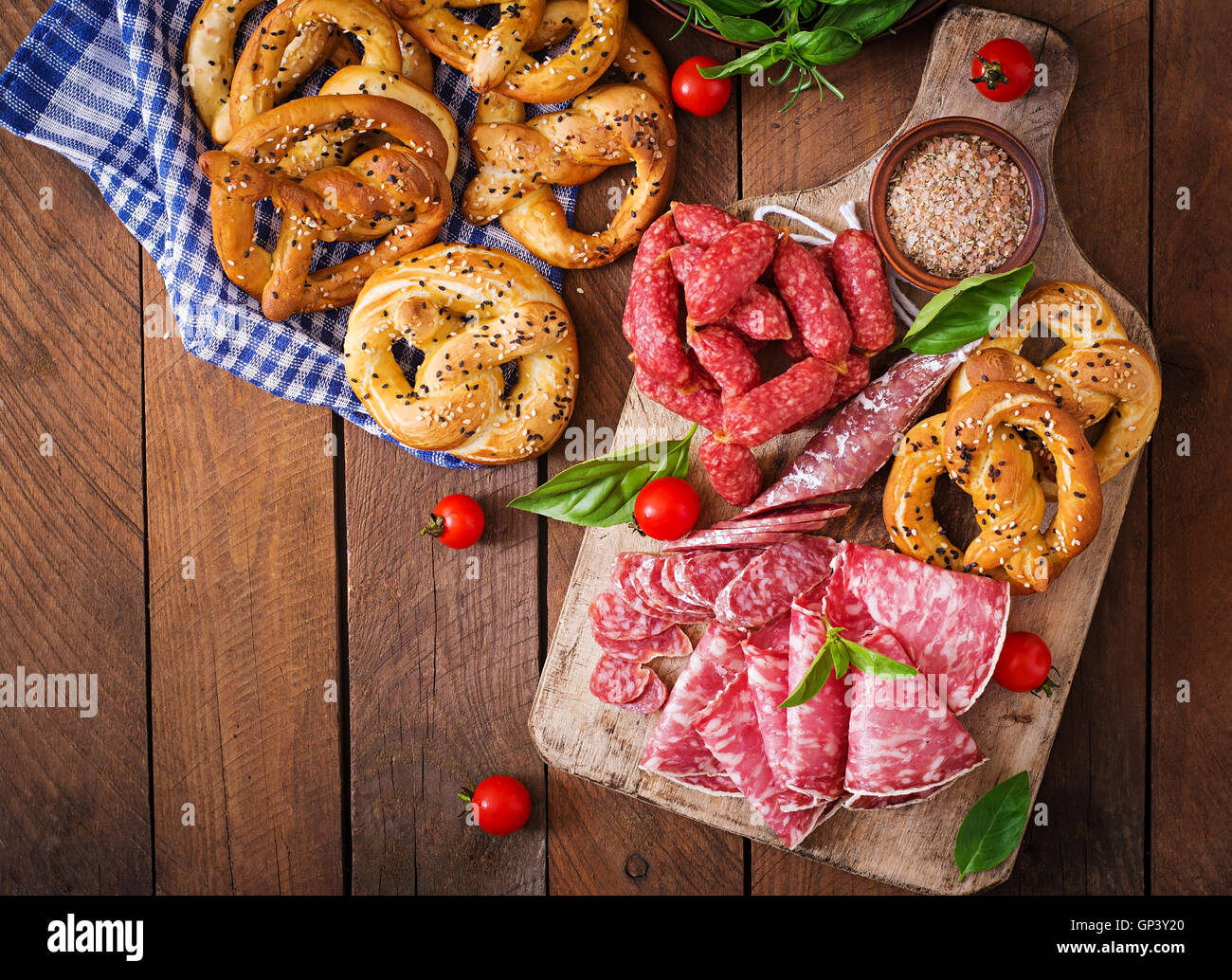 Pretzels and various sausages on wooden background. Oktoberfest. Stock Photo