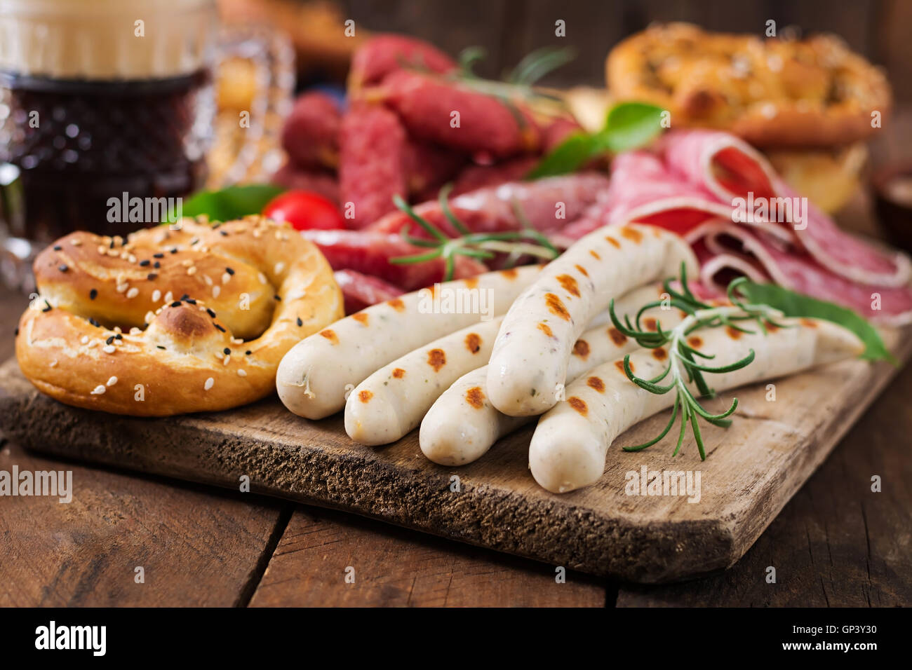 Glass of beer, pretzels and various sausages on wooden background. Oktoberfest. Stock Photo