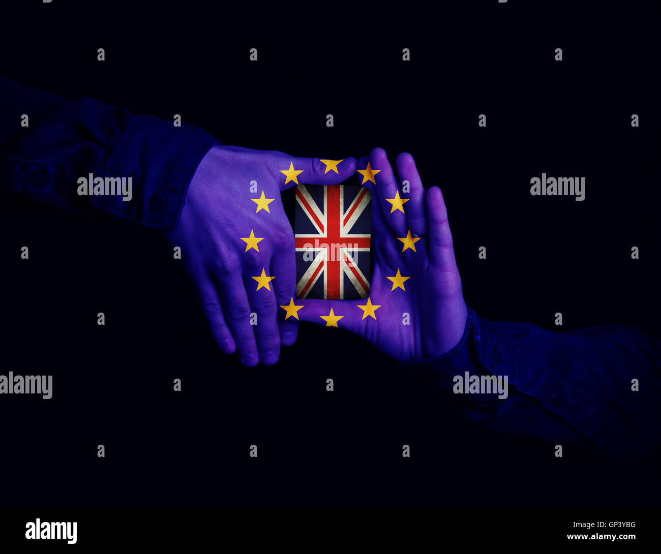 Close up of hands patterned with the flag of the European Community holding a card with the flag of the United Kingdom. - Stock Image