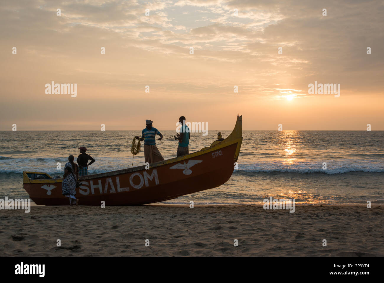 Fishermen preparing their nets and boat on Varkala beach, Kerala, India - Stock Image
