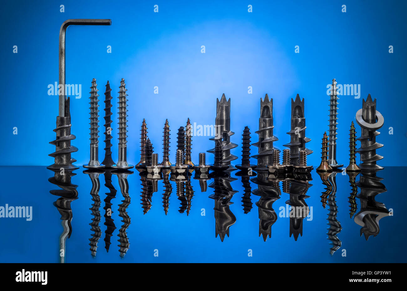 Collection of screws and bolts arranged as night time city skyline with rippled reflection in water effect. - Stock Image