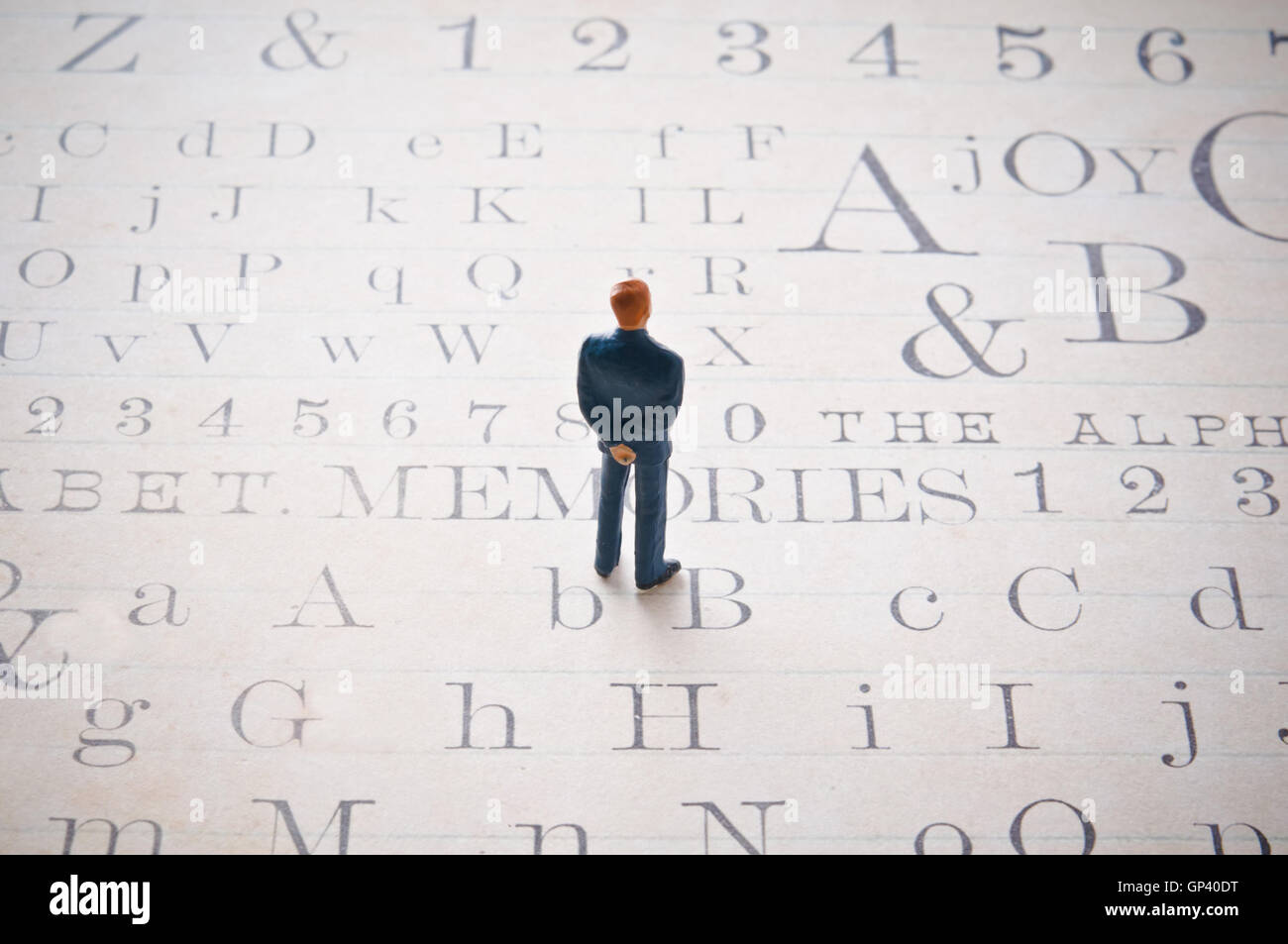 male miniature figurine standing on an alphabet page, literacy and culture concept - Stock Image