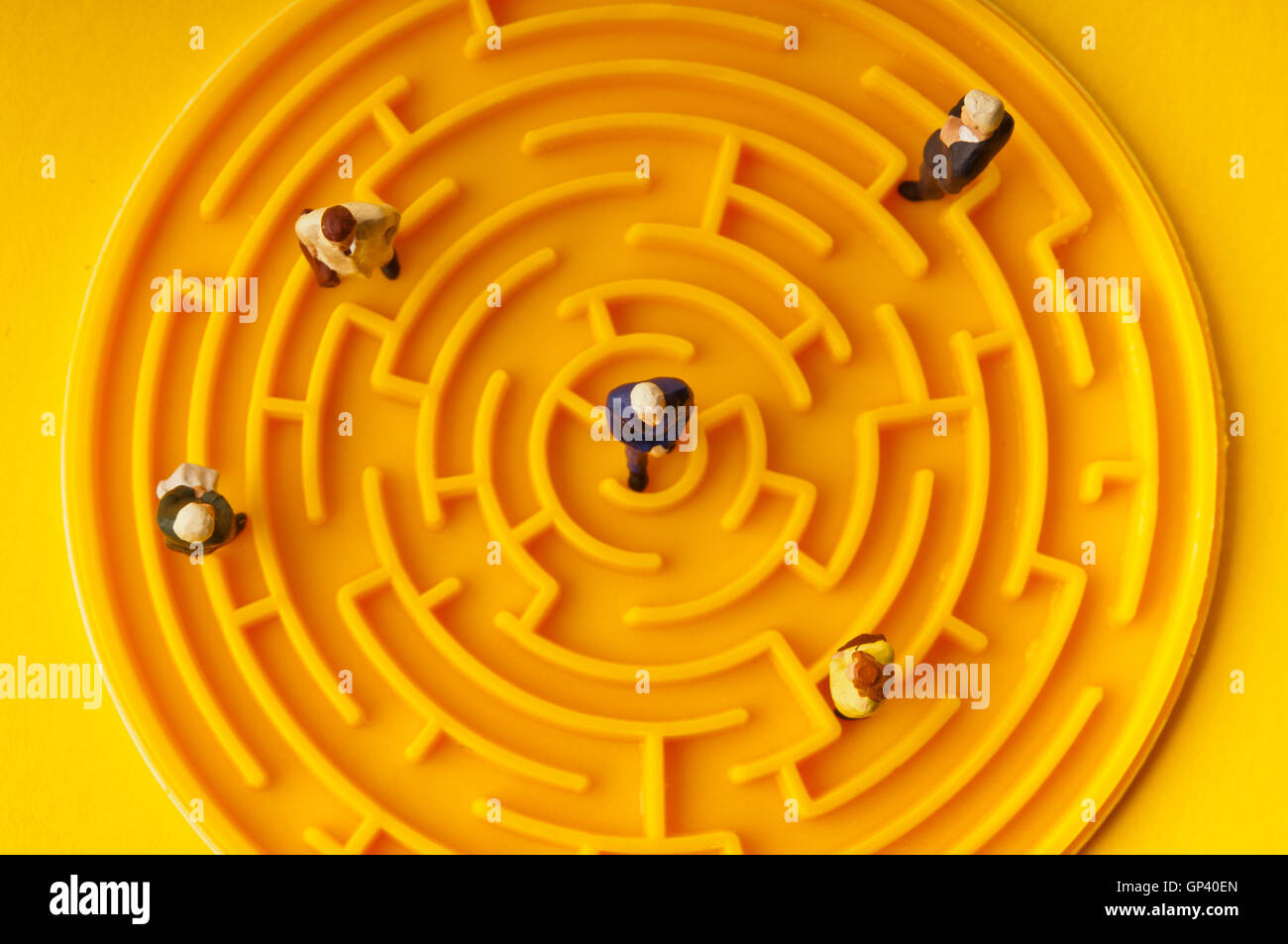 miniature figurines of people in a maze - Stock Image