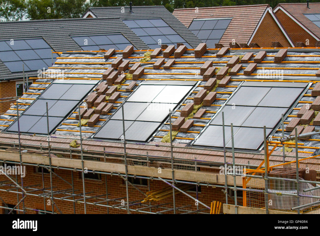 Redrow New Build houses under construction,  small energy efficient homes with roof tiles integrated solar panels, - Stock Image