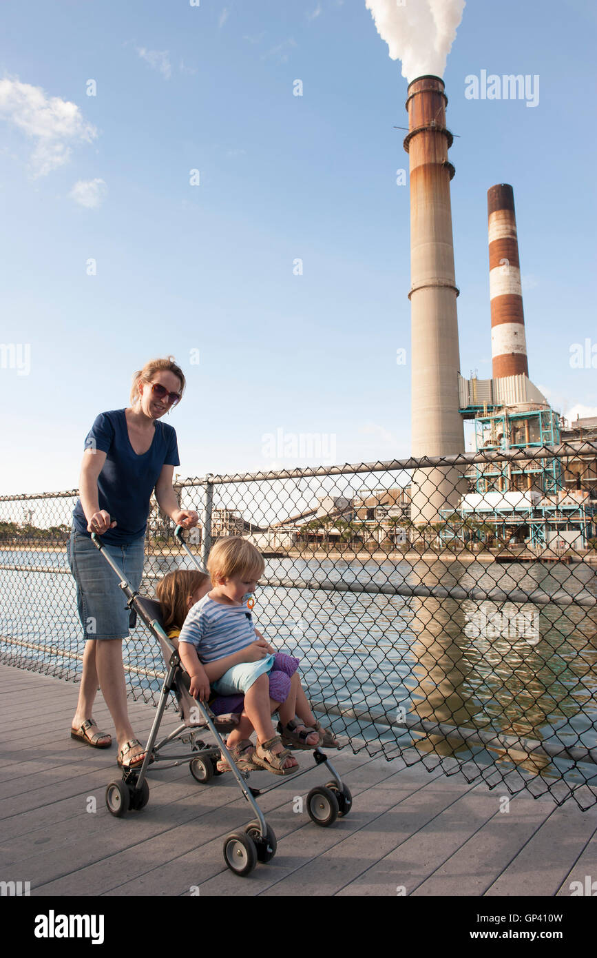Mother pushing children in stroller near power plant - Stock Image