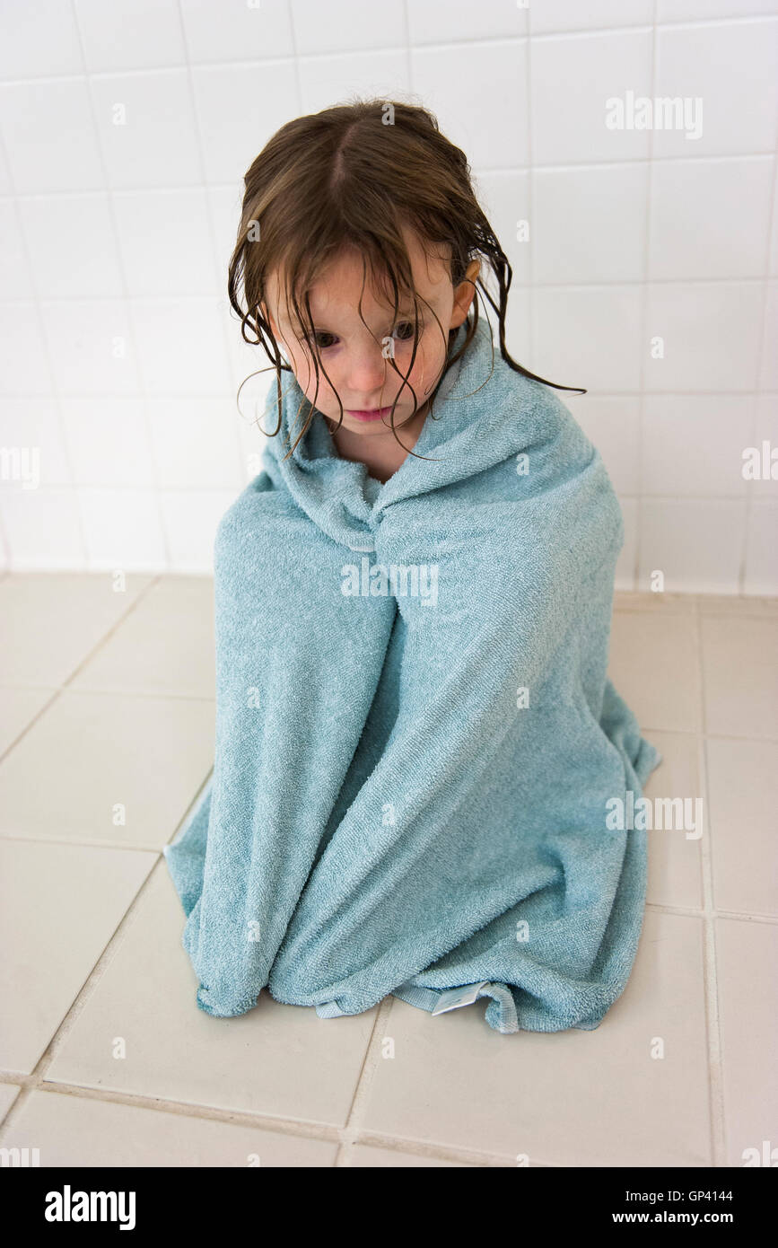 Little girl wrapped in a towel, looking down sadly - Stock Image