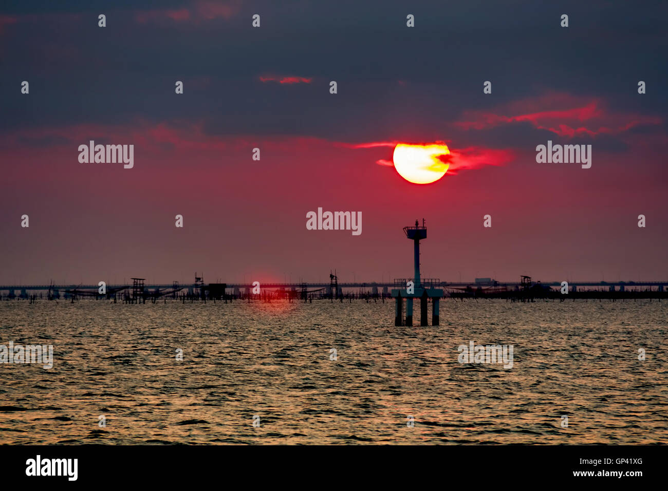 Partly cloudy sunset reflection sea. - Stock Image