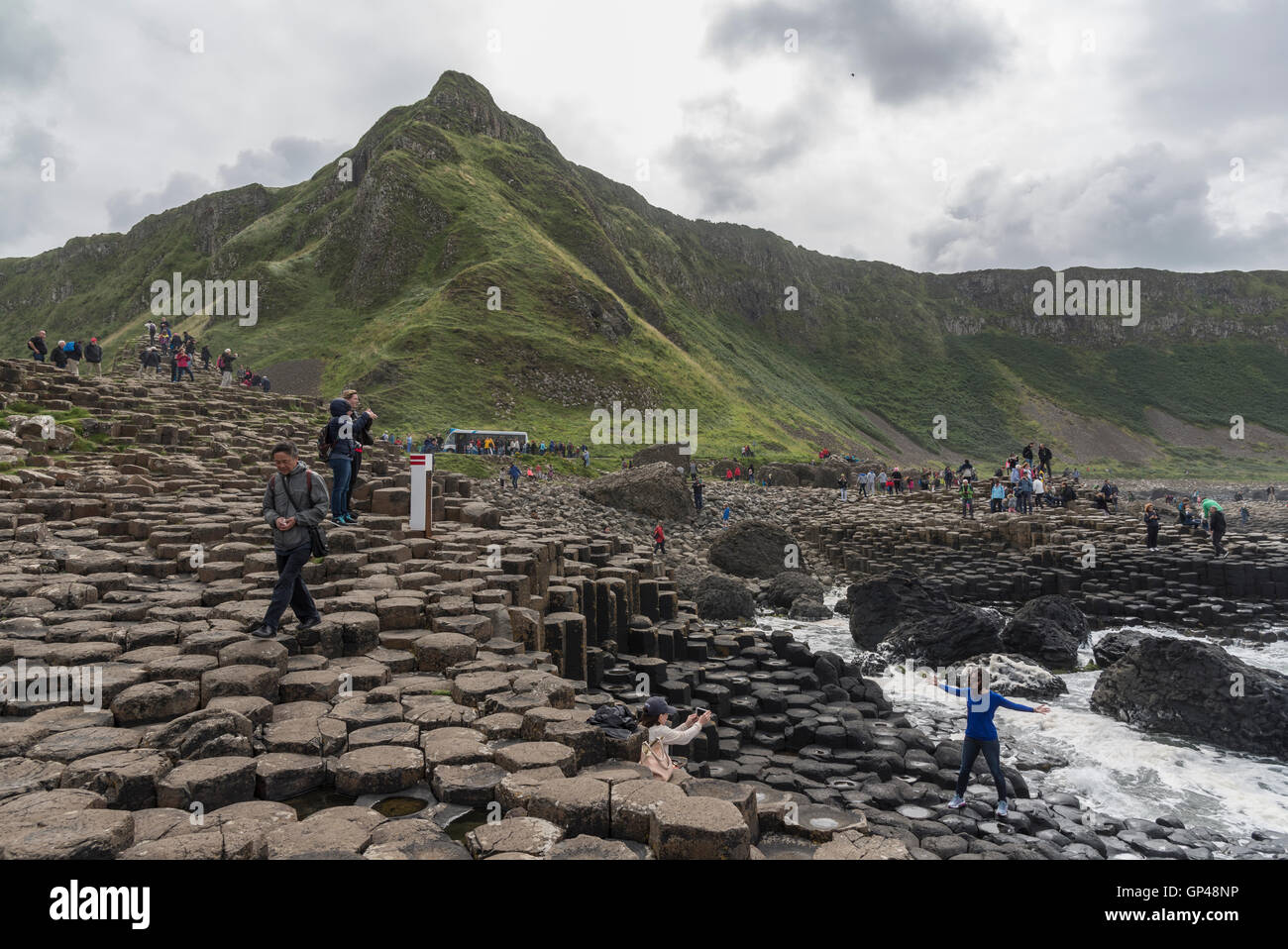 People walk around Giant's Causeway with hills in the background - Stock Image