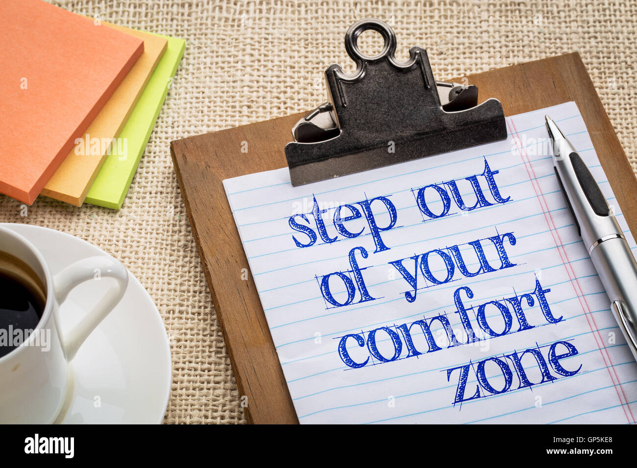 Step out of your comfort zone text on clipboard  with a pen, coffee and sticky notes against burlap canvas - office abstract Stock Photo