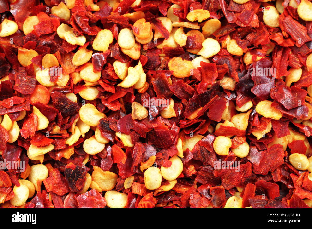 An extremely close up image of crushed red chilis - Stock Image