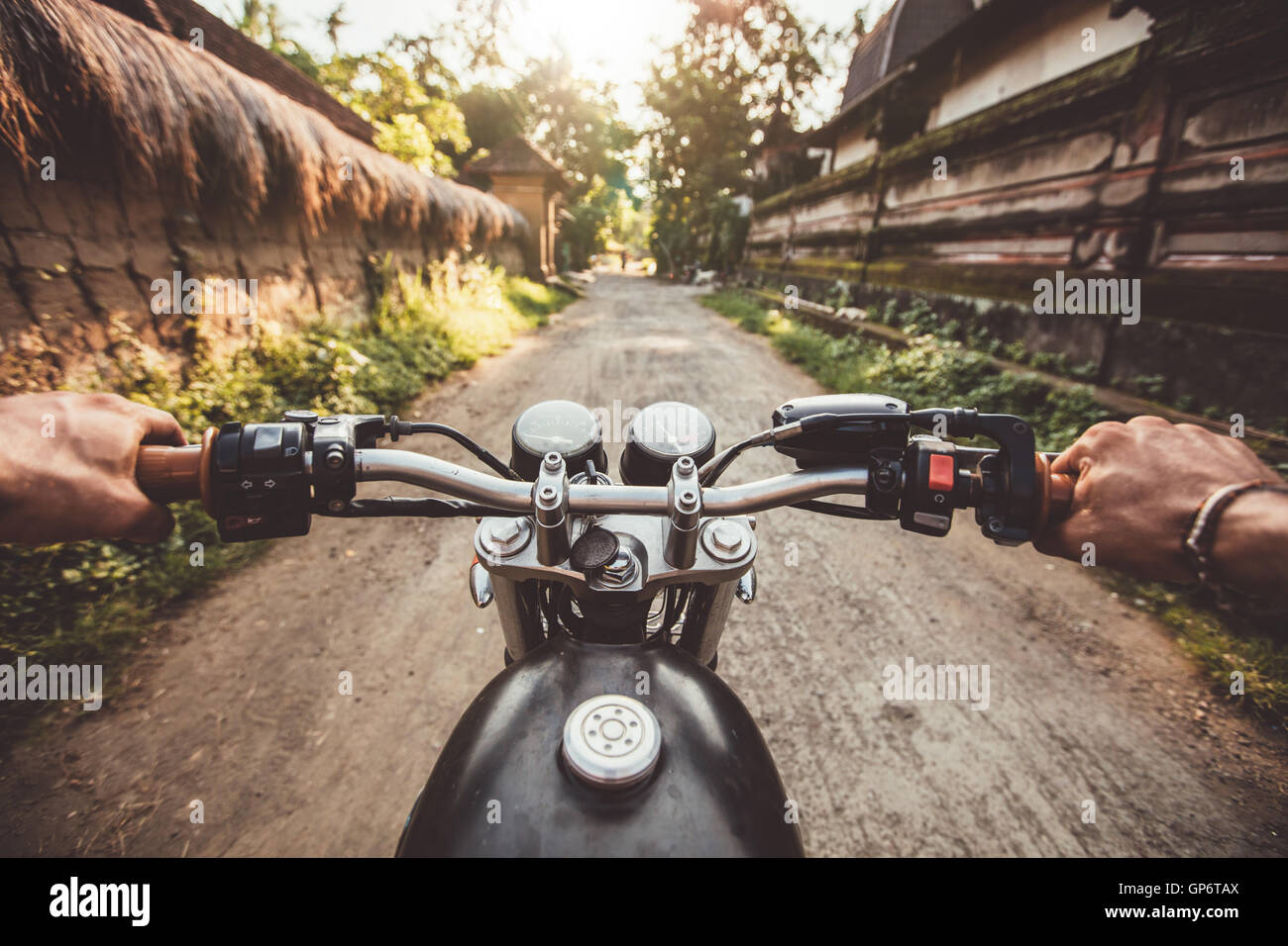 Biker driving his motorcycle on country road in a village. Point of view with focus is on the handlebar and man - Stock Image