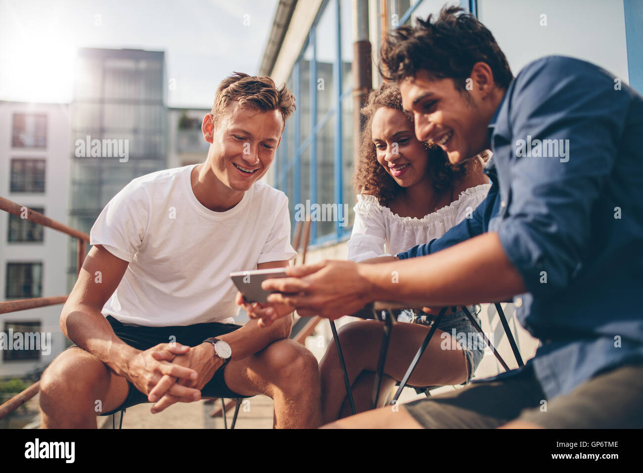 Group of people watching video on the mobile phone while sitting at outdoor cafe. Three young friends sitting outdoors - Stock Image