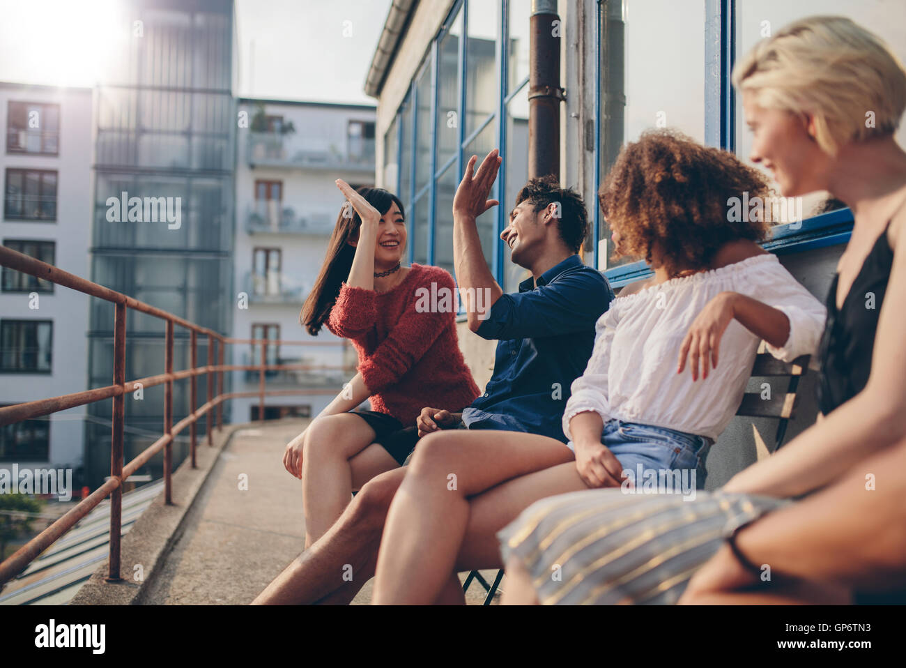 Multiracial group of friends having fun in balcony and giving high five. Young people enjoying in terrace. - Stock Image