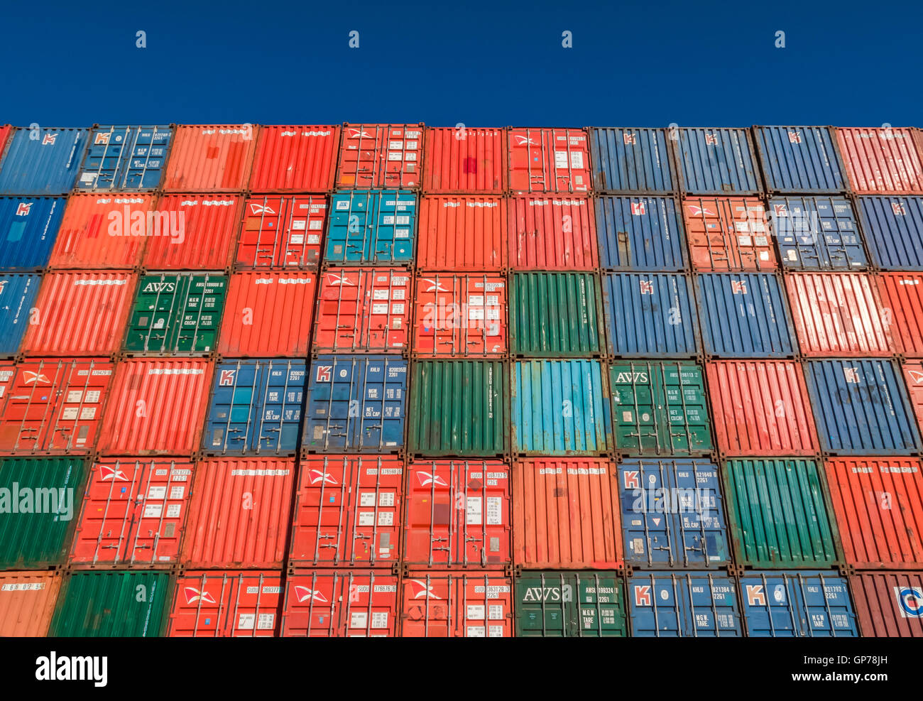 Wall of shipping containers stacked high - Stock Image