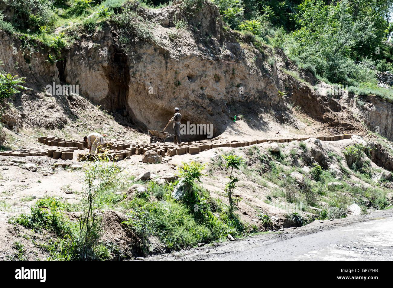 Two men making mud bricks beside the road to Ayun - Stock Image