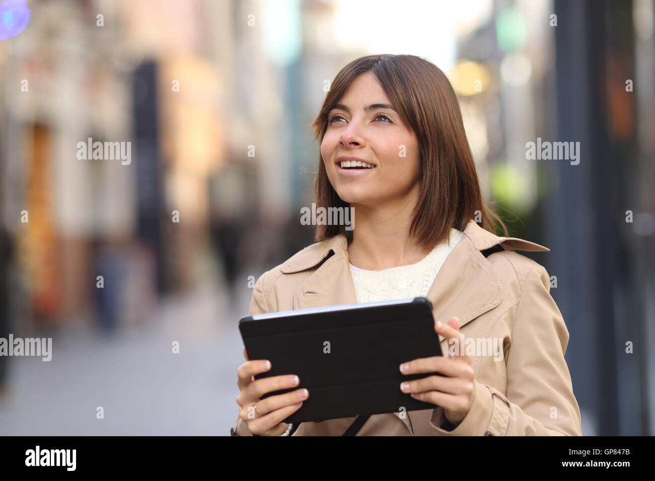 Tourist walking and consulting a guide in a tablet and watching amazed the street - Stock Image