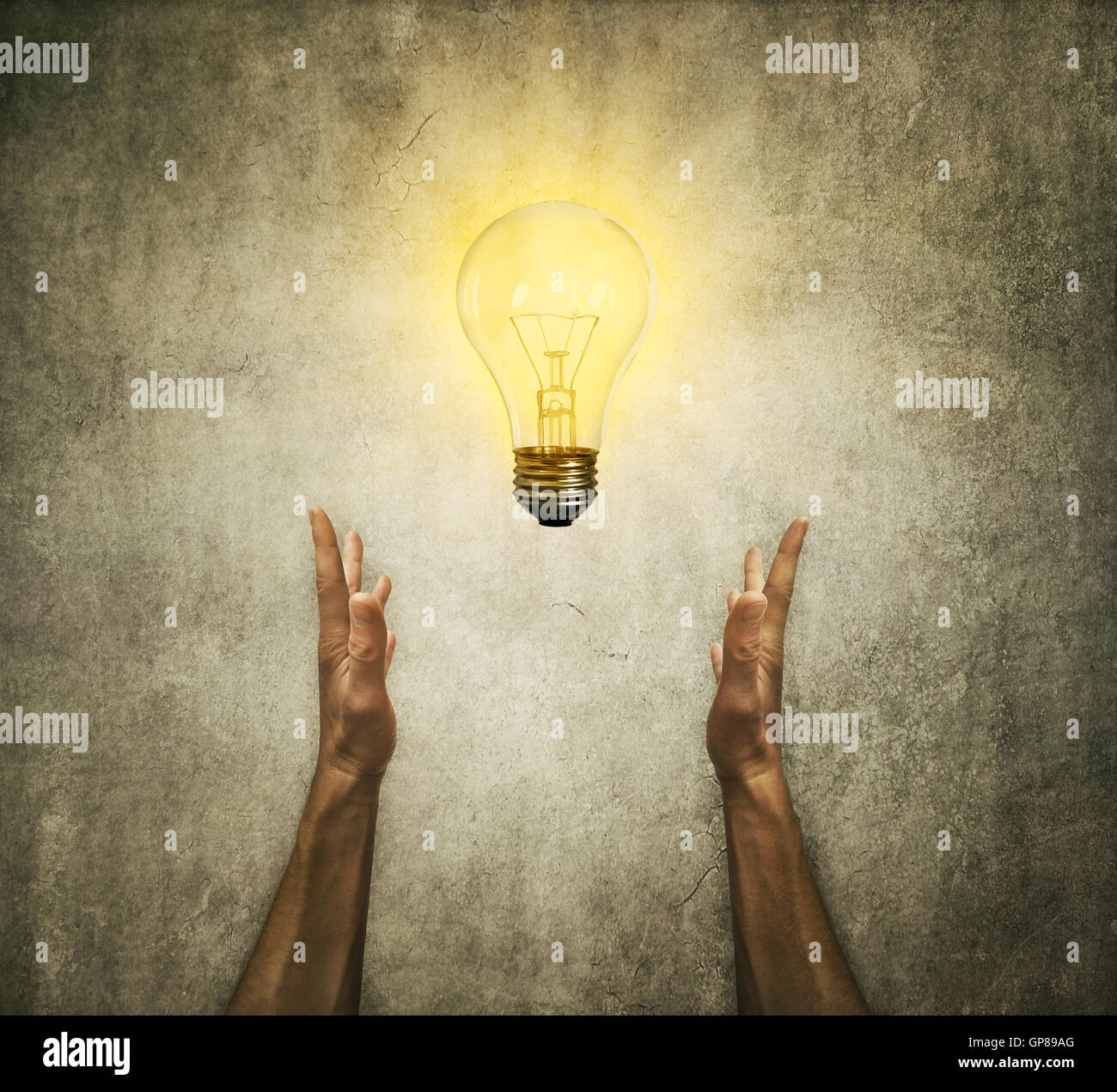 Closeup of two human hands holding a light bulb. Creativity and idea concept - Stock Image