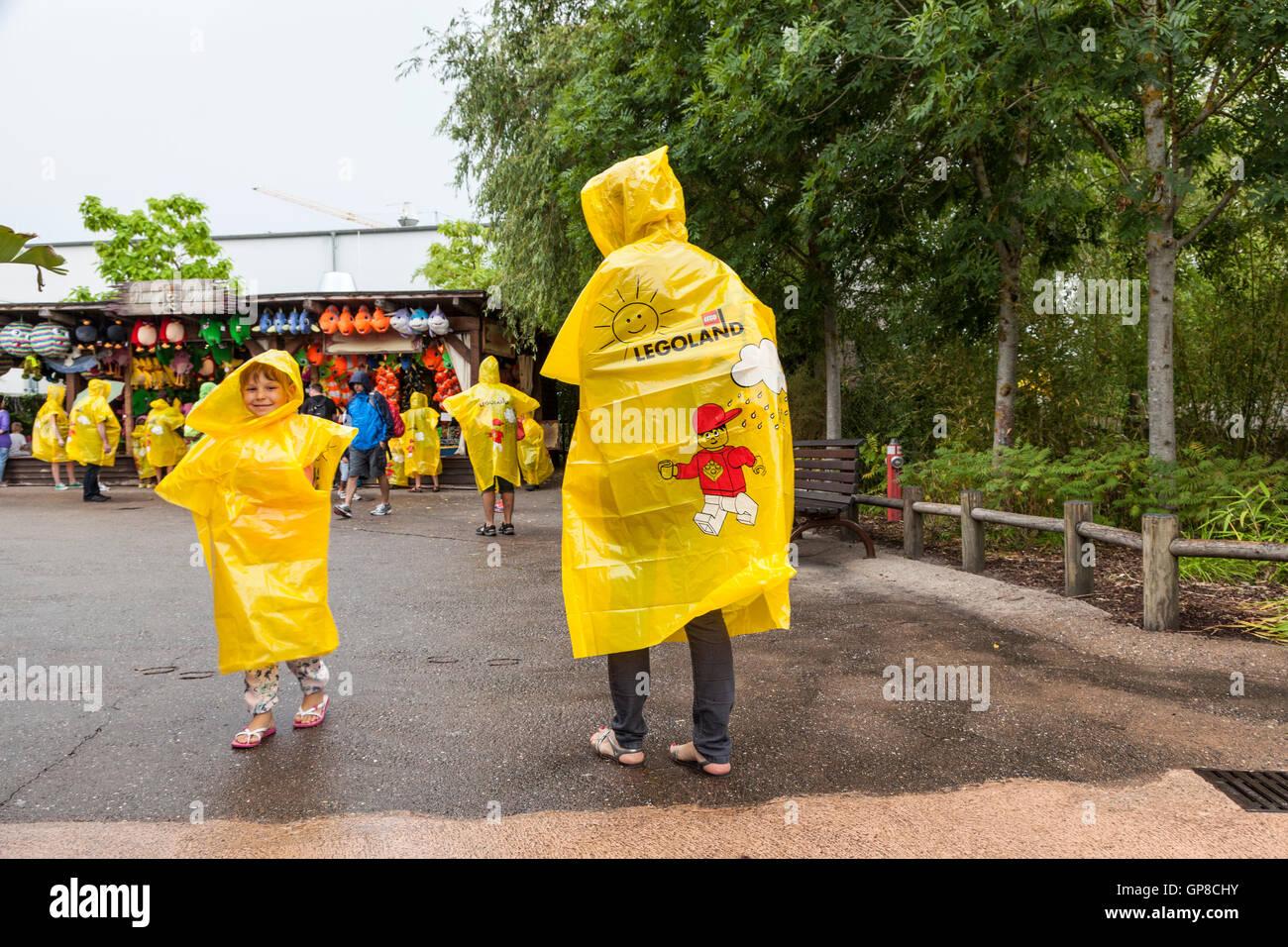Family wearing yellow Legoland Ponchos - Stock Image