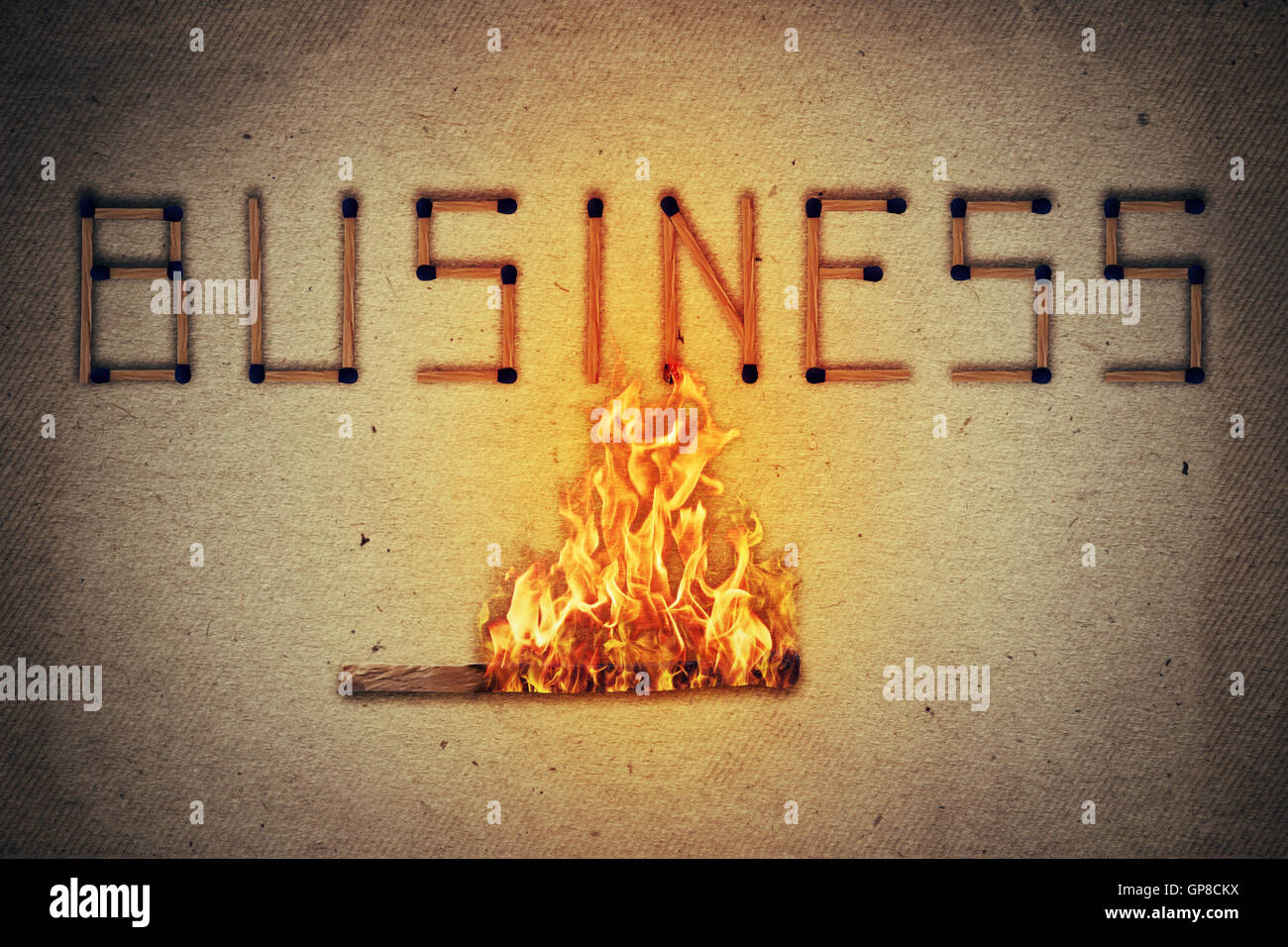 Burning match setting fire to its neighbors in arranged in shape of business word. Ignited match stick  as a symbol Stock Photo