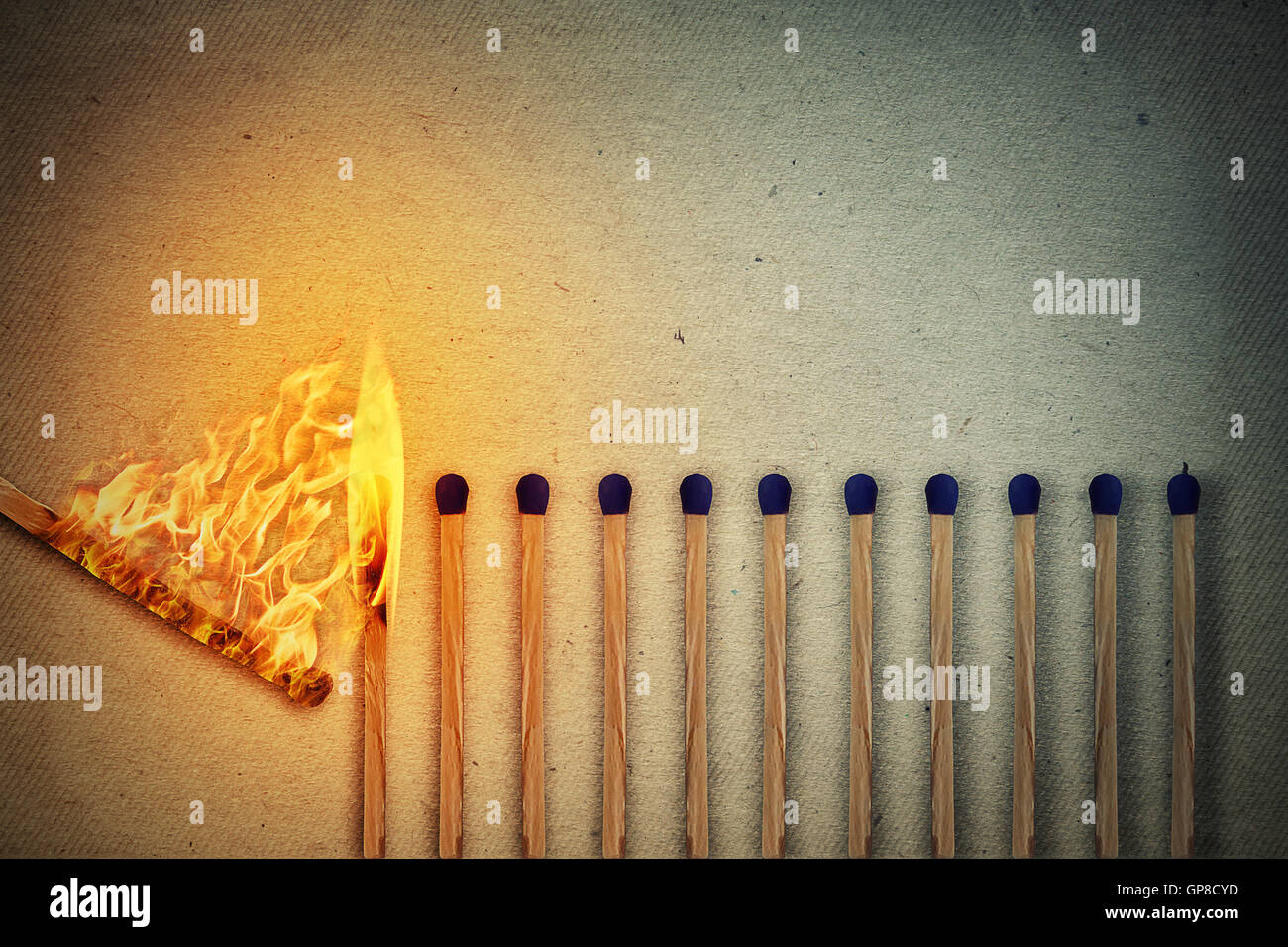 Burning match setting fire to its whole neighbors, a metaphor for ideas and inspiration. Leadership concept Stock Photo