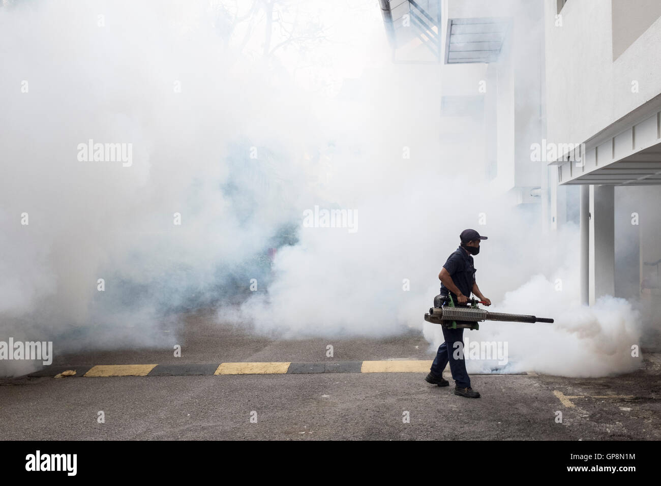 A worker fogs against mosquitoes around a condo in Kuala Lumpur, Malaysia. - Stock Image