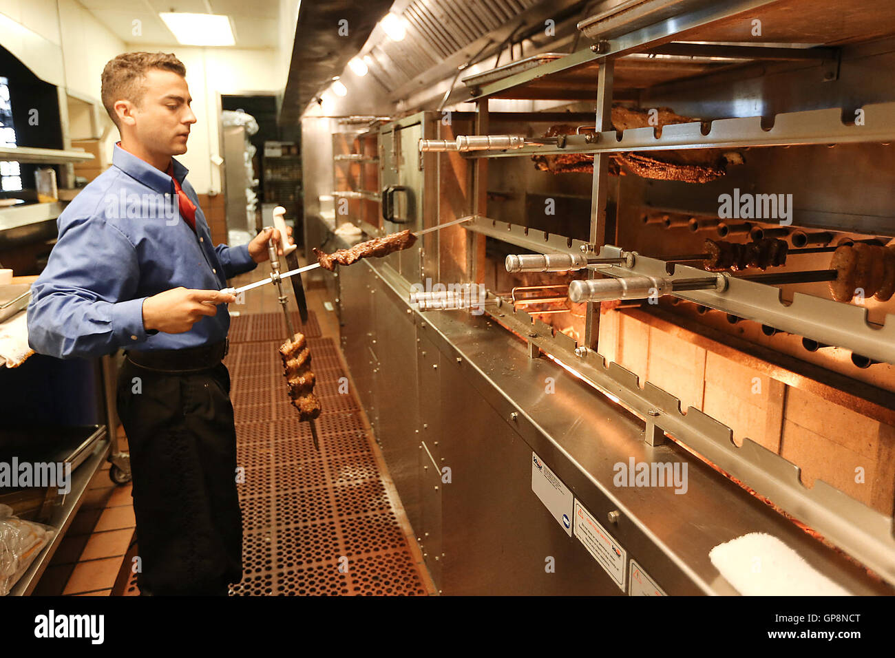 Napa, CA, USA. 26th Aug, 2016. Galpao Gaucho Brazilian Steakhouse gaucho chef Wagner Santos rotates skewers of meat - Stock Image
