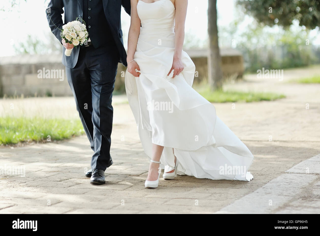 Bride and groom walking together in a park in wedding day - Stock Image