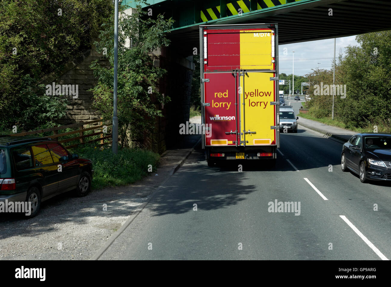 red,yellow,lorry,red lorry yellow lorry,driving under low bridge,pontefract,yorkshire,england,united kingdom - Stock Image