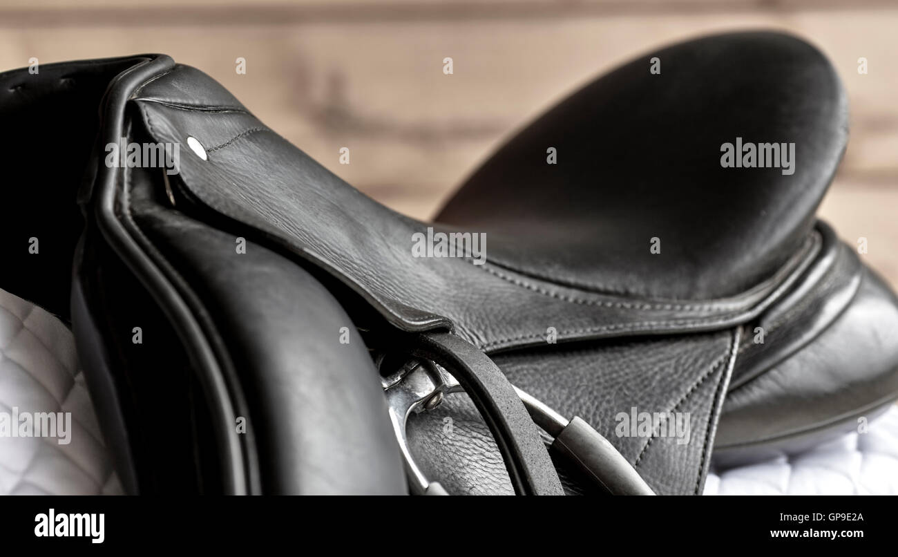Used black dressage horse riding saddle with  white saddle pad and shallow depth of field - Stock Image