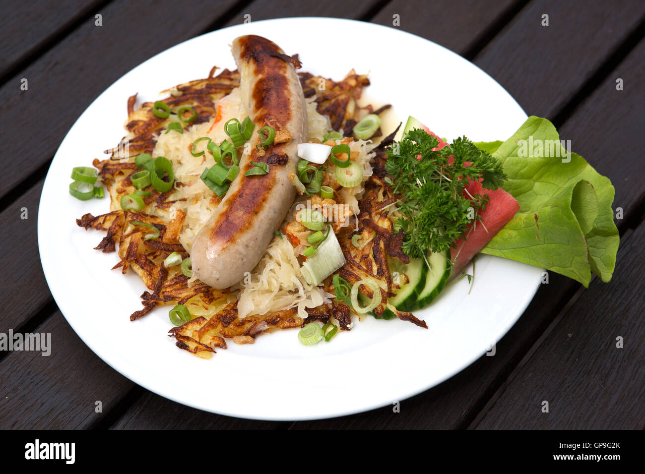 Thuringian bratwurst (grilled sausage) served with sauerkraut and salad in Thuringia, Germany. The dish is a regional Stock Photo