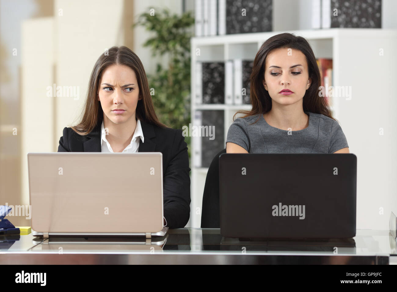 Front view of two angry businesswomen looking each other with hate working with laptops at office - Stock Image