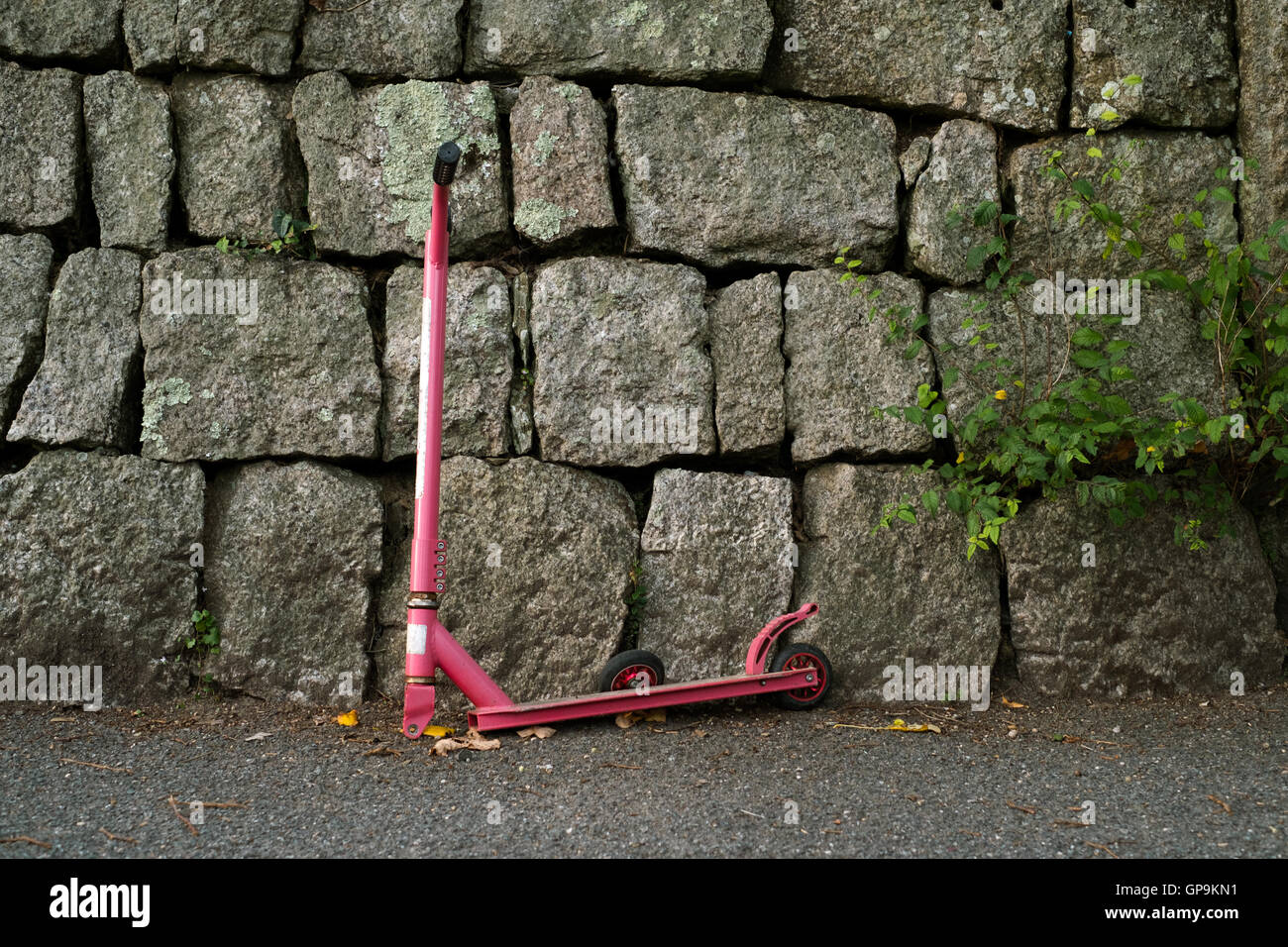 A child's pink scooter lays abandoned against a wall with a broken front wheel. - Stock Image