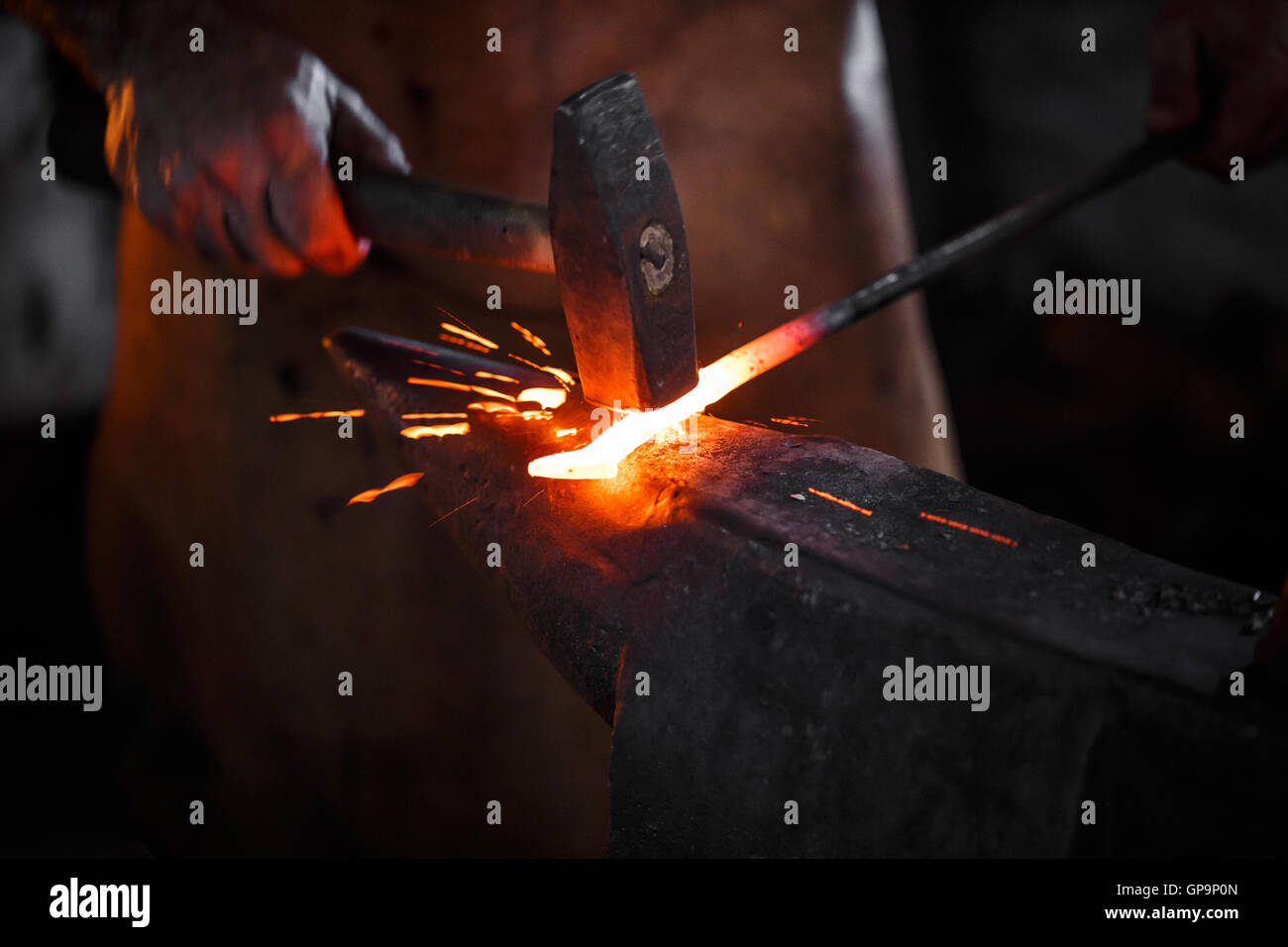 The blacksmith manually forging the molten metal on the anvil in smithy with spark fireworks - Stock Image