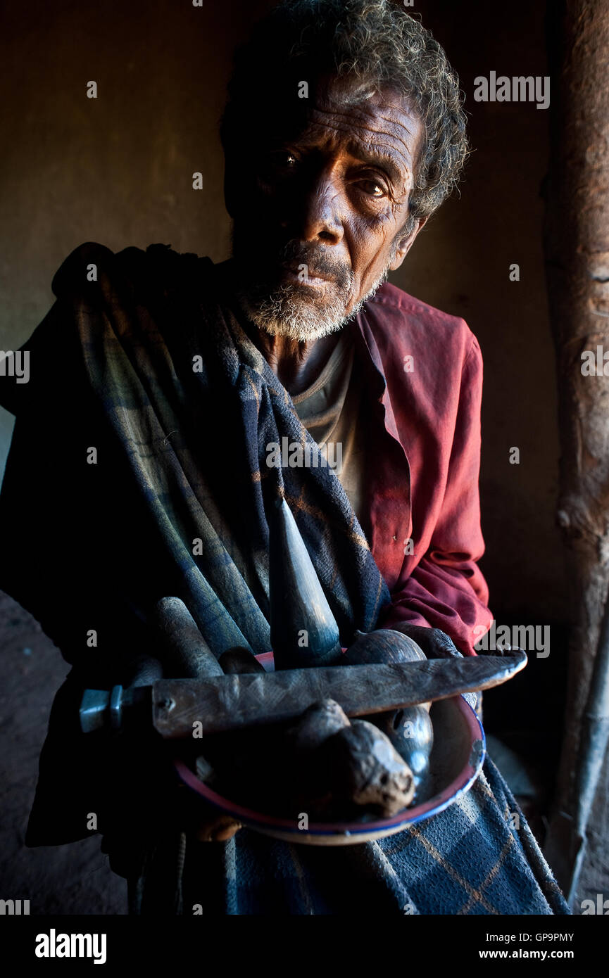 Traditional healer ('ombiasy') showing pieces of wood and a knife he uses to cure local people ( Madagascar) - Stock Image