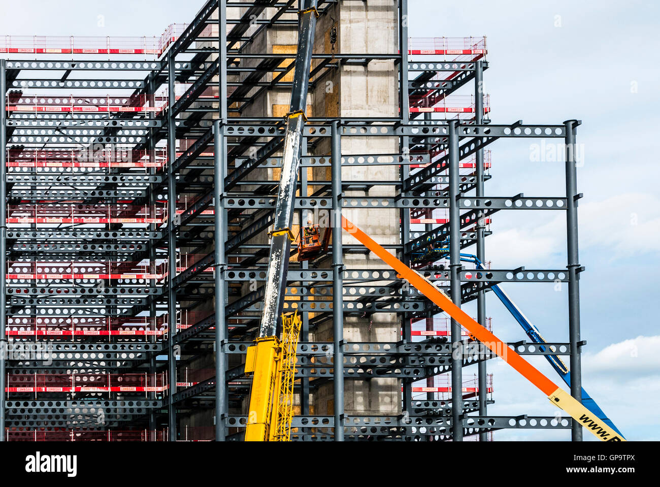 Cranes lift steel i-beams into place during the construction of a modern office block. Stock Photo