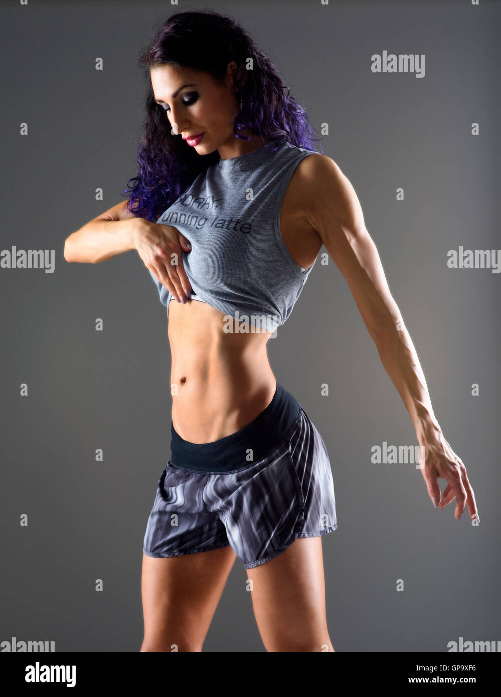 Toned woman looking at tummy - Stock Image